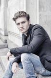 Attraktiver blonder junger Mann, der draußen sitzt Stockbilder