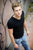 Attraktiver blonder junger Mann in der Stadtumwelt Stockfoto