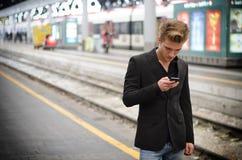 Attraktiver blonder junger Mann in der Station unter Verwendung des Mobiltelefons Lizenzfreie Stockbilder