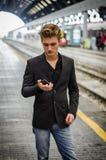 Attraktiver blonder junger Mann in der Station unter Verwendung des Mobiltelefons Lizenzfreies Stockbild