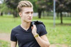 Attraktiver blonder junger Mann draußen in einem Park Lizenzfreie Stockfotografie