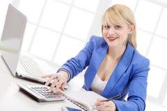 Attraktiver blonder Sekretär, der an ihrem Schreibtisch sitzt Stockbild
