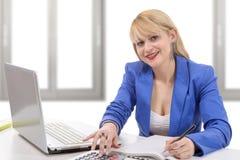 Attraktiver blonder Sekretär, der an ihrem Schreibtisch sitzt Stockfotos