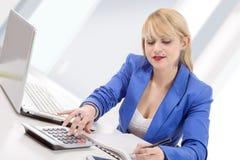 Attraktiver blonder Sekretär, der an ihrem Schreibtisch sitzt Lizenzfreie Stockfotos