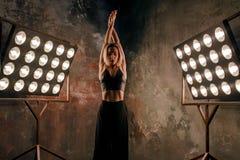 Attraktiver blonder Tänzer der jungen Frau auf dem Stadium mit Lichtern im Dachbodenhintergrund Lizenzfreie Stockbilder