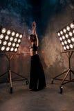 Attraktiver blonder Tänzer der jungen Frau auf dem Stadium mit Lichtern im Dachbodenhintergrund Stockfotografie
