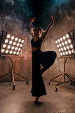 Attraktiver blonder Tänzer der jungen Frau auf dem Stadium mit Lichtern im Dachbodenhintergrund Lizenzfreie Stockfotos