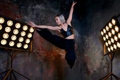 Attraktiver blonder Tänzer der jungen Frau auf dem Stadium mit Lichtern im Dachbodenhintergrund Stockfoto