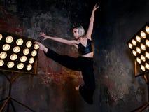 Attraktiver blonder Tänzer der jungen Frau auf dem Stadium mit Lichtern im Dachbodenhintergrund Stockbilder