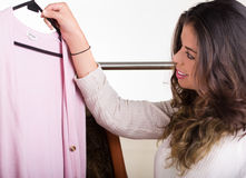 Attraktiver Brunette, der durch Kleidung auf Kleidungsgestell, Einkaufsmodekonzept schauend steht Stockfoto