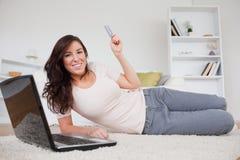 Attraktiver Brunette, der eine Zahlung mit einem Laptop leistet stockfoto
