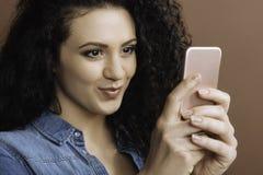 Attraktiver Brunette, der ihren Handy verwendet stockfoto