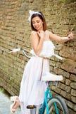Attraktiver Brunette, der mit blauem Fahrrad nahe alter Backsteinmauer aufwirft stockfotos