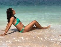 Attraktiver Brunette, der am Strand aufwirft stockfoto