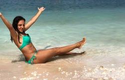 Attraktiver Brunette, der am Strand aufwirft stockfotos