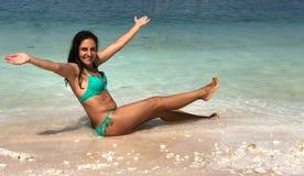Attraktiver Brunette, der am Strand aufwirft stockbilder