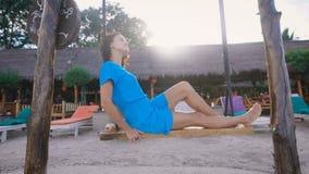 Attraktiver Brunette in der Türkiskleidung, die auf Schwingen auf Balinesestrand mit tropischem Haus und sunbeds in spielt stock video
