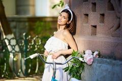 Attraktiver Brunette im weißen Kleid, das nahe rotem Gebäude mit ihrem blauen Fahrrad und Blumen steht stockfoto