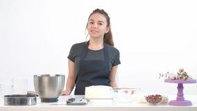 Attraktiver brunette Mädchenpatissier im Schutzblech peitscht Sahnekuchen in einer Metallschüssel stock footage