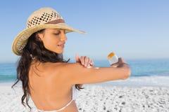 Attraktiver Brunette mit dem Strohhut, der auf Sonnencreme sich setzt Stockbilder