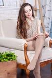 Attraktiver dünner junger Brunette trägt Strümpfe Sie sitzt in einem großen bequemen Stuhl Stockfotografie