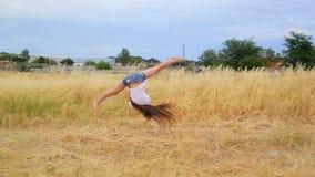 Attraktiver dünner Mädchenturner mit dem langen Haar kurz gesagt führt Übung rondat auf Feld mit goldenem Gras durch stock video
