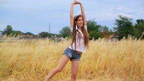 Attraktiver dünner Mädchenturner mit dem langen Haar kurz gesagt führt gymnastische Übung durch stock footage