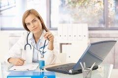 Attraktiver Doktorschreibensreport, der am Schreibtisch sitzt lizenzfreie stockbilder
