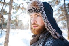 Attraktiver durchdachter bärtiger junger Mann im Winterhut Stockbilder
