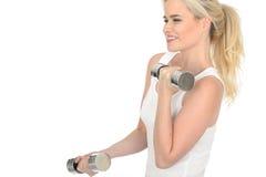 Attraktiver entschlossener Sitz-gesunde junge Blondine, die mit stummen Bell-Gewichten ausarbeiten Stockfoto