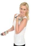 Attraktiver entschlossener Sitz-gesunde junge Blondine, die mit stummen Bell-Gewichten ausarbeiten Lizenzfreies Stockfoto