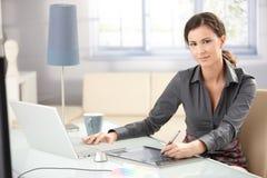 Attraktiver Entwerfer, der Tablette und Laptop verwendet Stockbild