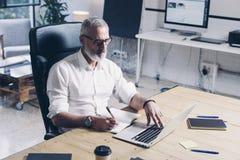 Attraktiver erwachsener Geschäftsmann unter Verwendung der mobilen Laptop-Computers beim Sitzen am Holztisch am modernen coworkin lizenzfreie stockfotos