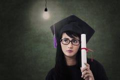 Attraktiver Frauabsolvent mit Zertifikat und gebeleuchteter Birne Stockfoto