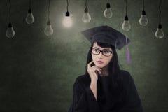 Attraktiver Frauabsolvent unter Lampen in der Klasse Lizenzfreies Stockfoto