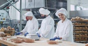 Attraktiver Frauenbäcker und ihre Kollegebäcker, die schnell in einer Backwarenindustrie bildet Stücke des Teigprozesses von arbe stock video