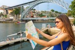 Attraktiver Frauenwanderer mit dem modischen Blick, der Richtung auf Karte beim Reisen im Ausland in Sommer sucht Stockfotografie