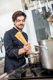 Attraktiver freundlicher Chef, der Spaghettis vorbereitet Lizenzfreies Stockfoto