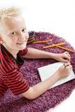 Attraktiver freundlicher Junge, der auf einer Wolldecke liegt Stockfotografie