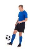 Attraktiver Fußballspieler in der blauen Uniform, die mit Ball isola spielt Lizenzfreie Stockfotografie