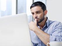 Attraktiver Geschäftsmann, der an Computer am Schreibtisch vor Wolkenkratzerfenster arbeitet stockfotografie
