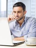 Attraktiver Geschäftsmann, der an Computer am Schreibtisch vor Wolkenkratzerfenster arbeitet lizenzfreie stockbilder