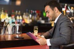 Attraktiver Geschäftsmann, der an der Stange sitzt Stockbilder