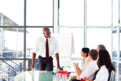 Attraktiver Geschäftsmann, der in einer Sitzung spricht Stockfotografie