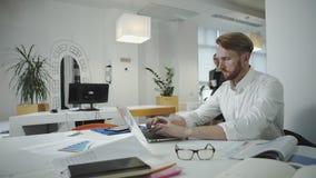 Attraktiver Geschäftsmann, der im Büro arbeitet und Fotorahmen betrachtet