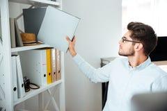 Attraktiver Geschäftsmann, der Ordner mit Dokumenten im Büro sitzt und nimmt Stockbilder