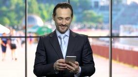 Attraktiver Geschäftsmann, der Telefon von seiner Jacke herausnimmt stock video footage