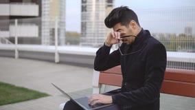 Attraktiver Geschäftsmann im schwarzen Anzug unter Verwendung des Laptopsitzens im Freien stockbild