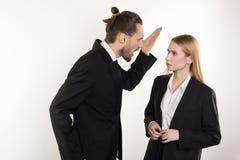 Attraktiver Geschäftsmann mit Bart und modische Frisur im schwarzen Anzug schreiend an seinem Untergebenen, der nicht fertig werd lizenzfreie stockbilder