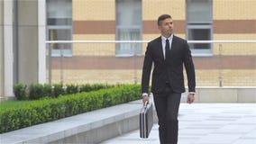 Attraktiver Geschäftsmann mit einem Koffer geht das Gebäude, Zeitlupe umher stock footage